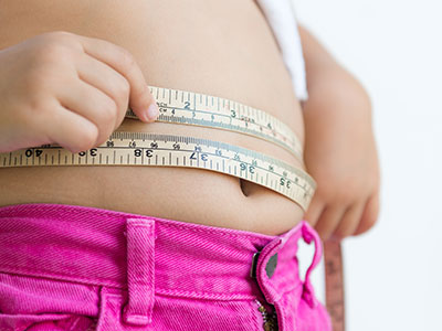child measuring belly with tape measure