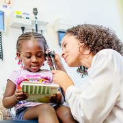 physician looking at little girl's ear