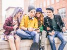 group of teenagers sitting on a wall