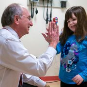 Roger Packer high fives patient Olivia Enos