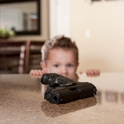 little boy looking at gun