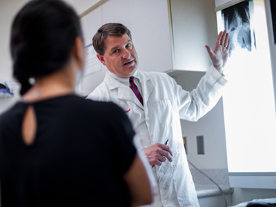Matthew Oetgen, M.D., discusses an image of a patient's spine.