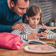 Girl using smartphone with dad