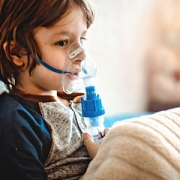 little boy using asthma inhaler