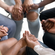 people sitting in a circle holding hands