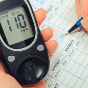 woman writing data to medical form and glucometer for checking sugar level