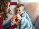 mother helping child with inhaler