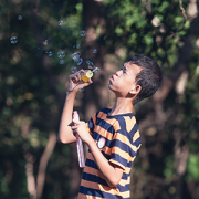 boy with autism blowing bubbles