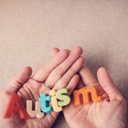 Hands holding letters that spell autism