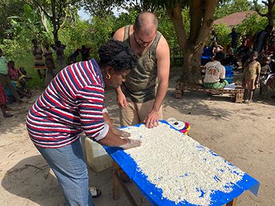 Dr. Nicole Mashukano and Dr. Matthew Bramble wetting cassava flour
