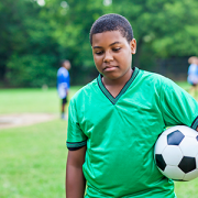 sad boy holding soccer ball