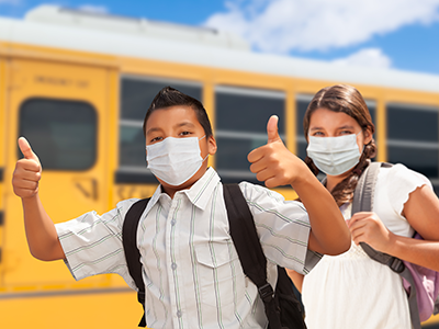 masked kids giving thumbs up in front of school bus